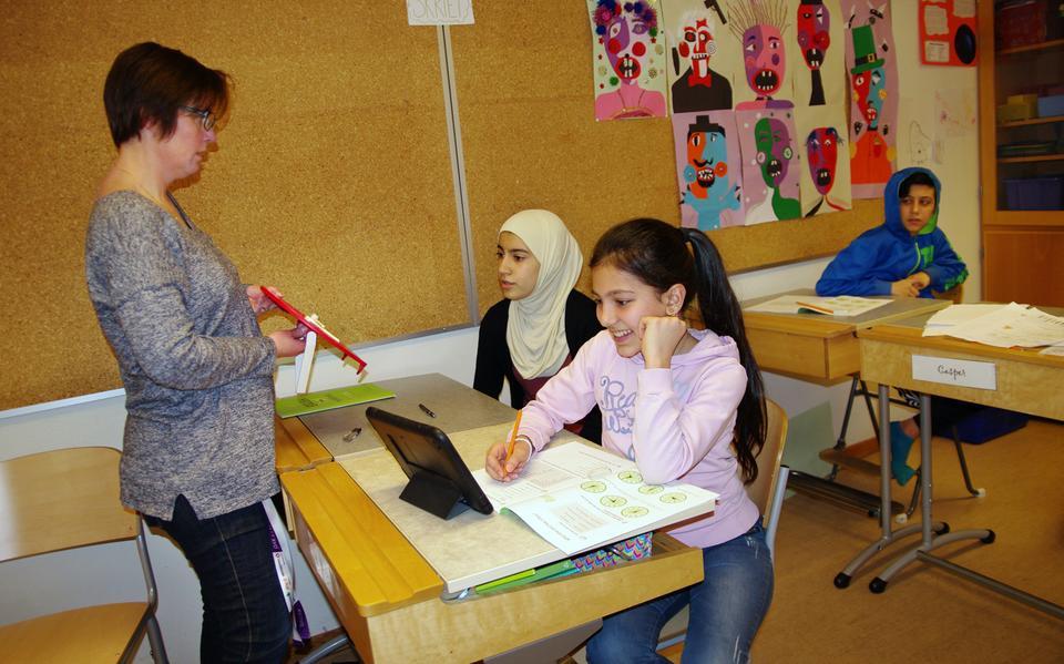 79a64be1 Eleverna i fokus. Camilla Henriksson, lärare i svenska och engelska,  hjälper sjätteklassarna Noor Alhoda Alammarin och Heba Hamsa med engelska  klockslag.